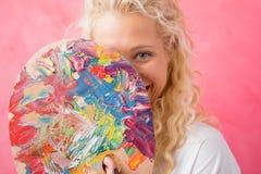 Artist hiding behind paint palette Stock Images