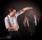 Artist hold big soap bubble in his hands. Royalty Free Stock Photos