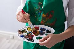 An Artist Holding Paint Palette And Paintbrush. Mid Section View Of An Female Artist`s Hand Holding Paint Palette And Paintbrush royalty free stock image