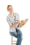 Artist Holding Palette And Paintbrush Sitting On Stool Stock Photo