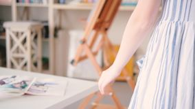 Artist inspiration female going touching desk art. Artist talent inspiration. Female going across home art studio gently touching workplace desk with sketchpads stock footage