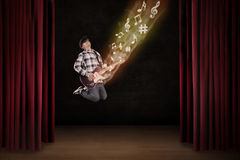 Artist jumping with guitar on stage Royalty Free Stock Photos