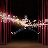 Artist jumping on stage playing guitar Royalty Free Stock Photos