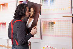 Artist kissing his created picture Royalty Free Stock Photo
