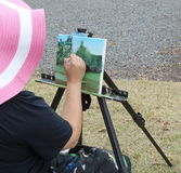 Artist lady sitting and painting on canvas outside. Royalty Free Stock Photography