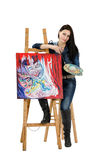 Artist leaning on an easel with abstract painting Metamorphosis. Beautiful woman artist leaning on an easel with her abstract painting Metamorphosis on white royalty free stock photography