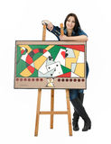 Artist leaning on an easel with her abstract painting Stock Image