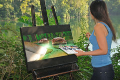 Artist looking at the scenery while painting on canvas Royalty Free Stock Image