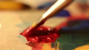 Artist lowers the brush in red paint and mixes it on the palette. Macro shooting stock video