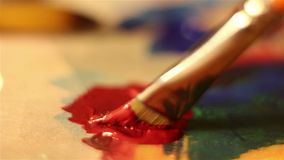 Artist lowers the brush in red paint and mixes it on the palette. Macro shooting stock footage
