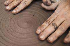 Artist makes clay pottery on a spin wheel. Close up detail view at an artist makes clay pottery on a spin wheel royalty free stock images