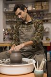 Artist makes clay pottery on a spin wheel in workshop. View at an artist makes clay pottery on a spin wheel in workshop stock photography