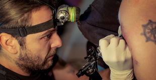 Artist making tattoo on male customer. `s shoulder in studio Royalty Free Stock Images