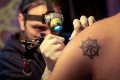 Artist making tattoo on male customer. `s shoulder in studio Stock Image