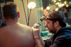 Artist making tattoo on male customer. `s shoulder in studio Stock Photography