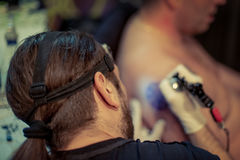 Artist making tattoo on male customer. `s shoulder in studio Royalty Free Stock Image