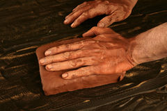Artist man hands working red clay for handcraft. Artist man hands working red clay to create handcraft art royalty free stock image