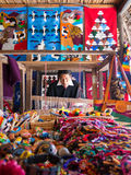 Artist man weaves with a loom in Ecuador. A man weaves pieces of fabric art on his loom in Ecuador surrounded by decorative objects and creations Stock Photo