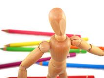 Artist Mannequin. Wooden artist mannequin with colored pencils in the background Royalty Free Stock Photography