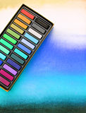 Artist media, chalk pastels on watercolor wash. A photograph showing a box of high quality artists chalk pastels, on a background of graduated watercolour wash Royalty Free Stock Image
