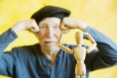 Artist Mimics a Wooden Figure Stock Images