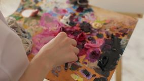 The artist mixes oil paints on a palette with a brush, close-up. The artist works in a drawing Studio stock footage