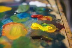 Artist mixes oil paints on pallet with various. Colors design stock images