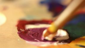 Artist mixes on the palette white and red paint. Macro shooting stock footage