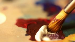 Artist mixes on the palette white and red paint. Macro shooting stock video footage