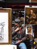 Artist at Monmartre, Paris. Monmartre, Paris, France - June 3, 2013: Artist sitting in the street among his works on display for sale to tourists. Paris, 2013 stock image