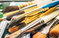 Artist Paint Brushes. A collection of artist's paint brushes resting on a  palette Stock Photography