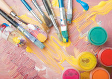 Artist paint brushes and color containers on colorful background Stock Image