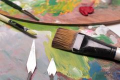 Artist paint brushes,palette knifeand oil paint on wooden artist. Ic palette background. Brush paint artistic. Tools for creative work. Back to school. Paintings stock photography