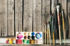 Artist paint brushes and palette on wooden background. Royalty Free Stock Images