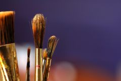 Artist paintbrush. Paintbrushes on a dark blue background close up one paintbrush is clear the others are blurred Royalty Free Stock Image