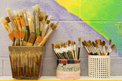 Artist paintbrushes. Containers of various sizes of clean artist paintbrushes against a colorful wall painting royalty free stock photos
