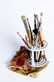 Artist paintbrushes and cleaning cloth. Artist brushes holder with a bunch of old pencils and brushes of different kinds, and a stained cleaning cloth Stock Image
