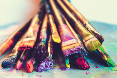 Artist paintbrushes with paint closeup on artistic canvas. Retro toned. Selective focus royalty free stock photos