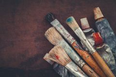 Artist paintbrushes, paint tubes closeup on brown canvas background. Copy space for text stock image