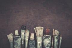 Artist paintbrushes, paint tubes closeup on dark canvas background. Stock Photography