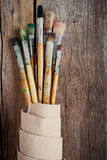 Artist paintbrushes and roll of canvas. On wooden background stock photo