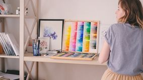 Artist lady tidying workplace arranging supplies stock video