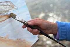 Artist painting. A close up of a mature artists hand painting a coastal landscape Royalty Free Stock Images