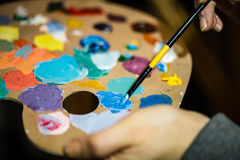 Artist painting with acrylic colors and mixing tones Royalty Free Stock Images
