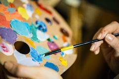 Artist painting with acrylic colors and mixing tones Royalty Free Stock Photos