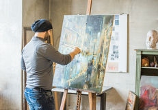 Artist painting on canvas. Artist/painter dressed in jeans and a grey top drawing/painting on canvas in his art studio stock images