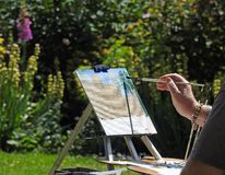 Artist painting on canvas watercolour outdoor summer hobby. Photo of a man wearing a summer hat with paints and brushes painting a garden scene located at royalty free stock image