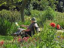 Artist painting on canvas watercolour outdoor summer hobby. Photo of a man wearing a summer hat with paints and brushes painting a garden scene located at royalty free stock photo