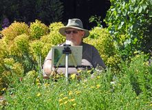 Artist painting on canvas watercolour outdoor summer hobby. Photo of a man wearing a summer hat with paints and brushes painting a garden scene located at stock image