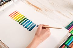 Artist painting colorful stripes with brush on white paper. Artist painting colorful gradient stripes with watercolor paint and brush on white paper Stock Image